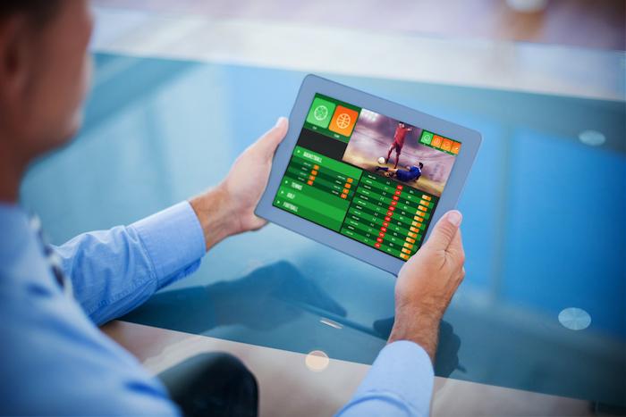 Mann besucht Sportwetten-Seite per Tablet.