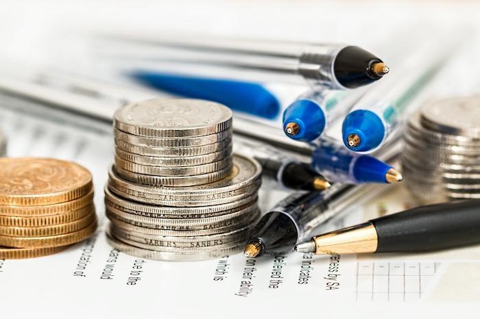 Geld und Kugelschreiber zum ausfüllen von Sportwetten liegen auf einem Blatt Papier