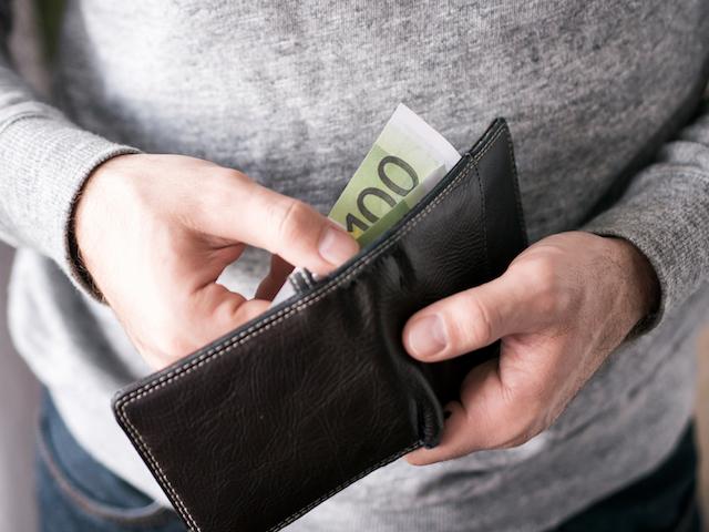 Mann steckt Geldschein in seine Geldbörse.