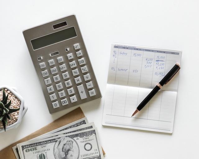 Ein Taschenrechner, Geldscheine und ein Block mit Stift auf einem Tisch liegend