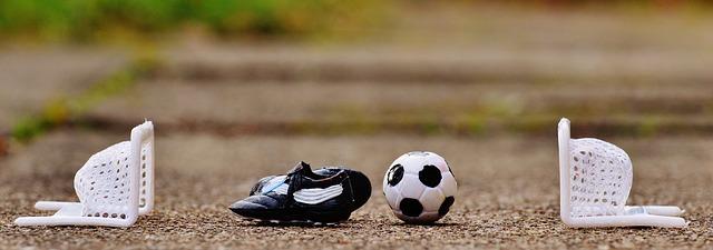 Sportwetten im Fußball - Zwei Minitore mit einem Ball und Fussball-Schuh in der Mitte