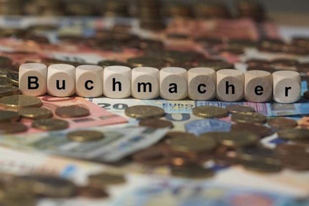 Buchmacher in Holzbuchstaben auf Geldstücken - Wettbörse