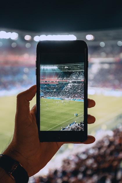 Ein Handy in der Hand nimmt ein Fußballspiel im Stadion auf.